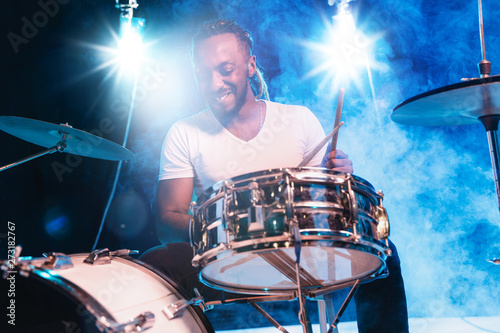 Young african-american jazz musician or drummer playing drums on blue studio background in glowing smoke around him. Concept of music, hobby, inspirness. Colorful portrait of joyful attractive artist. - 273182767