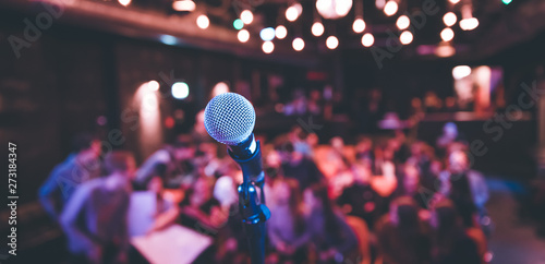 Event hall: Close up of microphone stand, seats with audience in the blurry background - 273184347