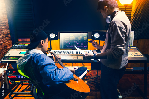 male asian producer consulting with professional guitarist about style of a song to record in recording studio - 273184906