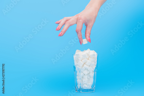 Fototapety, obrazy: partial view of woman holding sugar cube near glass full of white sugar cubes isolated on blue