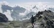 Aerial of man run on ridge edge.Trail runner running to mountain top peak training on rocky cliff.Wild green nature outdoors at sunrise or sunset backlit. Activity,sport,effort,challenge,willpower