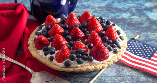 Fényképezés  A Strawberry and Blueberry Fresh Summer Pie on a Distressed Blue Wooden Table