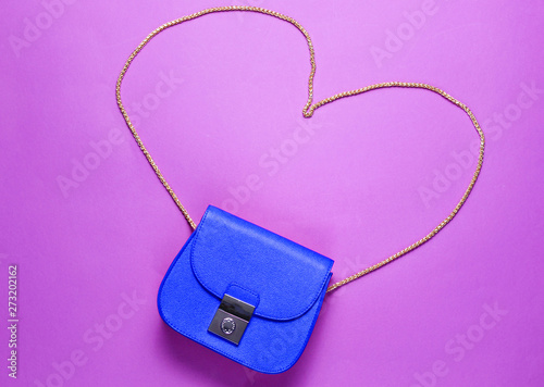 In de dag Hert Blue leather mini bag with heart-shaped chain on purple background. Minimalism love and fashion concept. Top view