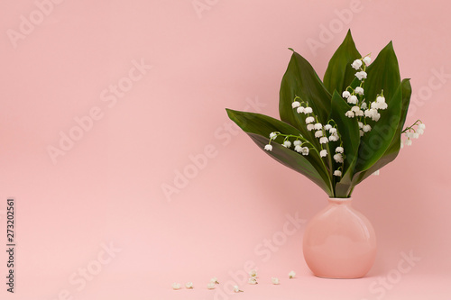 Photo Stands Lily of the valley Bouquet of lily of the valley in a pink vase and white flowers of lily of the valley on a pink background