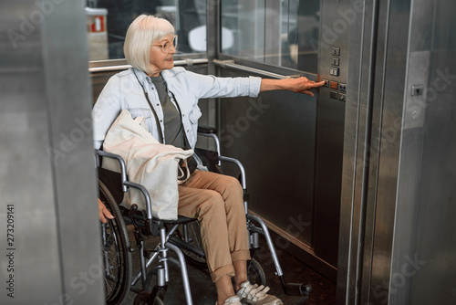 Photo Mature woman in glasses on disabled carriage using elevator