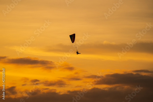 Foto op Canvas Luchtsport The silhouette of the paramotor at sunset