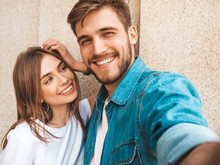 Smiling Beautiful Girl And Her Handsome Boyfriend In Casual Summer Clothes. Happy Family Taking Selfie Self Portrait Of Themselves On Smartphone Camera. Having Fun On The Street Background