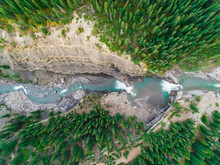 Aerial View Above Of A Waterfall Falling Between Pine Tree Forest, Alberta, Canada.