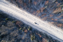 Aerial View Of A Blue Car Driving In The Snowy Forest In Estonia.