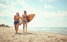 Friends Happy Surfer Girls Walking With Board On The Sandy Beach..