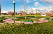 Green Benches Around A Circular Pathway On A Park With Trees And Lamp Posts