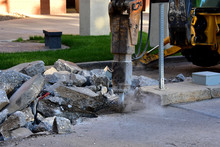 Backhoe With Jackhammer Tool Breaking Up Concrete Driveway.