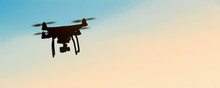 Quadrocopters Silhouette Against The Background Of The Sunset ..