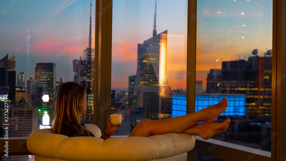 Fototapety, obrazy: CLOSE UP Woman relaxes in sofa chair with a cup of tea while observing cityscape