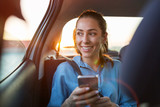 Young woman with smartphone on the back seat of a car - 273230741