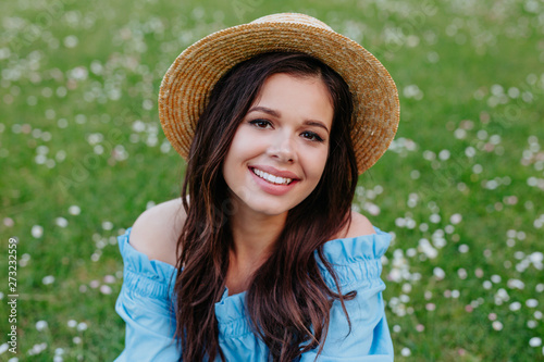 bcc9c205 beautiful young brunette woman in straw hat on the meadow with white  flowers on a warm