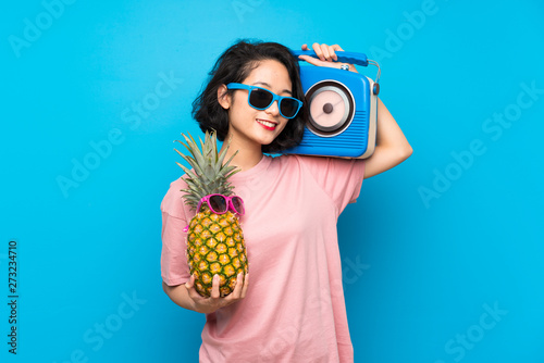 Asian young woman over isolated blue background holding a pineapple with sunglasses and a radio - 273234710