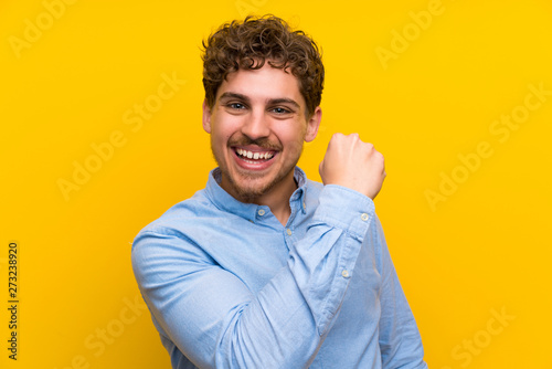 Photographie Blonde man over isolated yellow wall celebrating a victory