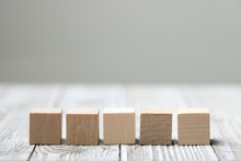Five Wooden Toy Cubes Arranged In Row On White Grey Wooden Background