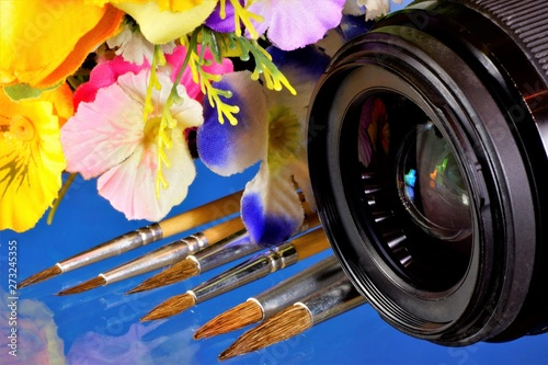 Photo Camera lens, summer flowers and artist's brushes