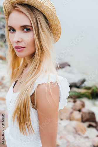 attractive blonde woman in straw hat and white dress looking at camera