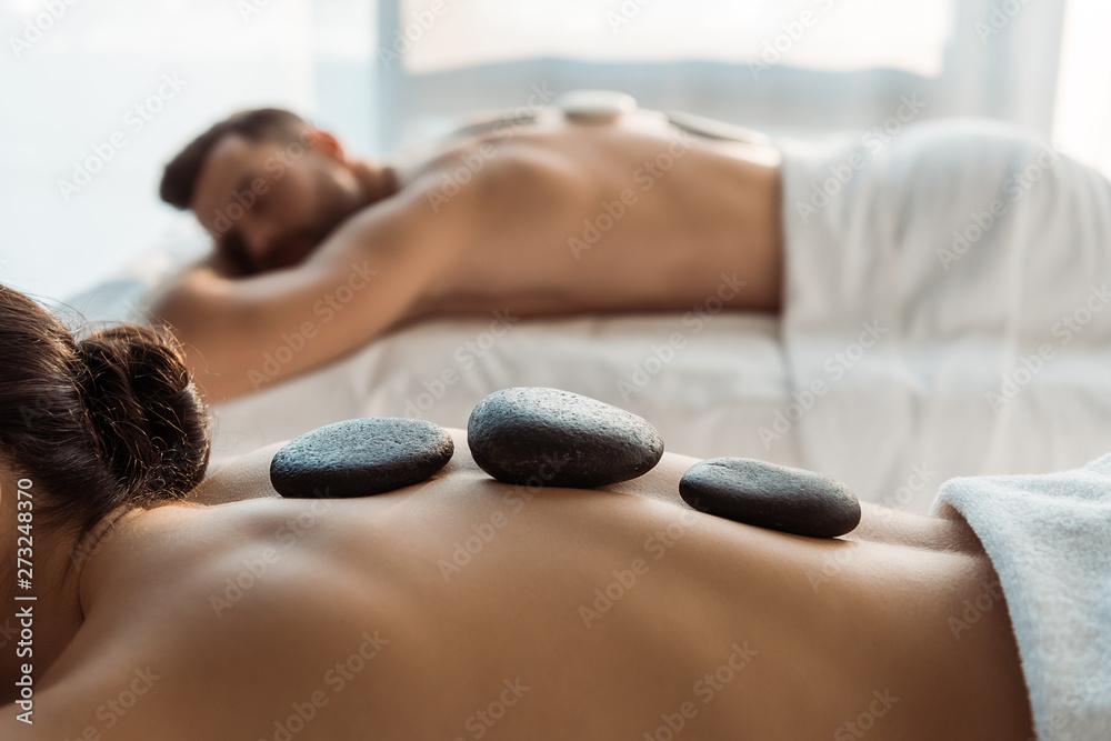 Fototapeta selective focus of woman having stone massage near man in spa center