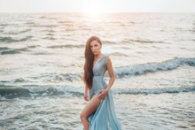 Queen Of Sea Emerged From Ocean And Threateningly Looks At World Of Dry Land, Long Haired Brunette Beauty Poses In Long Gentle Blue Dress And Shows Bare Long Leg, Mysterious Mermaid, Wave Daughter