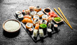 The range of different types of sushi, rolls and Maki with sauces and chopsticks.