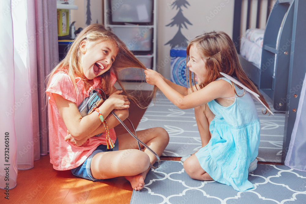 Fototapety, obrazy: Two little mad angry girls sisters having fight at home. Friends girls can not share toy bag. Lifestyle authentic funny family moment of siblings quarrel. Kids bad behaviour.
