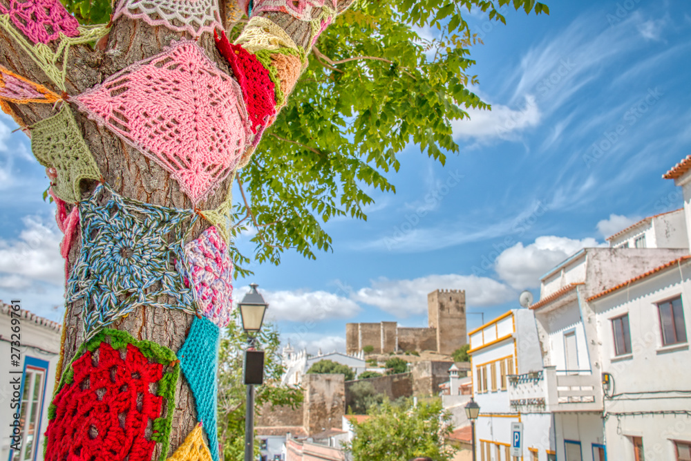 Fototapeta Trees decorated with colorful crochet patchwork on a holiday in the town of Mertola, a very beautiful city in the Portuguese Alentejo area