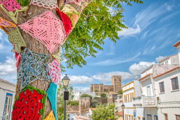 Trees decorated with colorful crochet patchwork on a holiday in the town of Mertola, a very beautiful city in the Portuguese Alentejo area