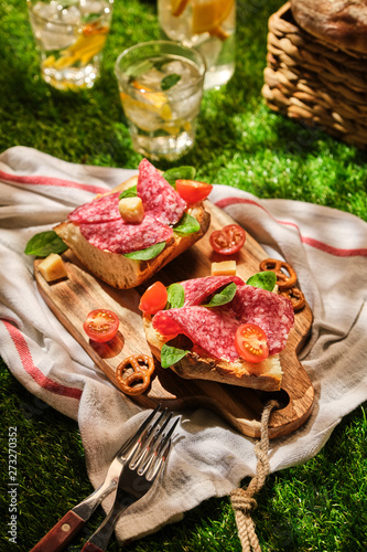 Sandwiches with salami. Picnic on the grass. Breakfast al fresco. Sandwiches with sausage, tomatoes and cheese