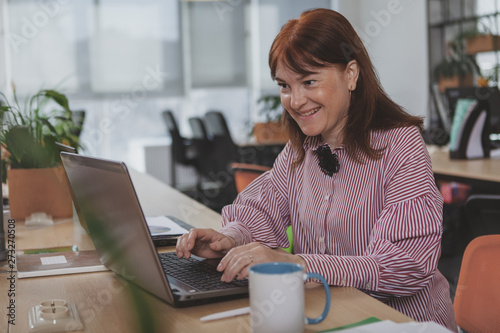 Fototapeta Cheerful mature businesswoman smiling, working at her office. Lovely female entrepreneur typing on her laptop, copy space. Happy woman using computer at workplace obraz na płótnie