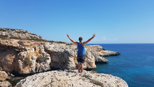 A Young Man Standing At The Steep Cliff And Spreading His Arms Wide In A Gesture Of Freedom In Cape Greco, Cyprus. Blue Sea Spreads In Front Of Him. Barren Slopes Of The Cliff. Endless Horizon Line.