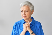 Portrait Of Serious Frowning Middle Aged Mature European Woman With Gray Pixie Hair Expressing Nervousness, Holding Clasped Hands On Her Chest, Being Impatient, Waiting For Results Of Blood Test