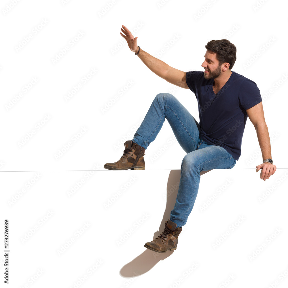 Fototapety, obrazy: Happy Handsome Man Is Sitting On A Top, Looking Away And Waving Hand