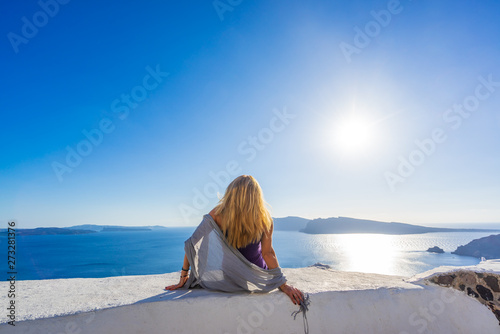 Foto  Luxury travel vacation woman looking at view on Santorini island
