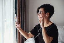 Portrait Of  Healthy Middle Aged Asian Woman Making Facetime Video Calling With  Smartphone, Using Zoom Meeting Online App, Work From Home, Working Remotely, Social Distancing, New Normal Concept