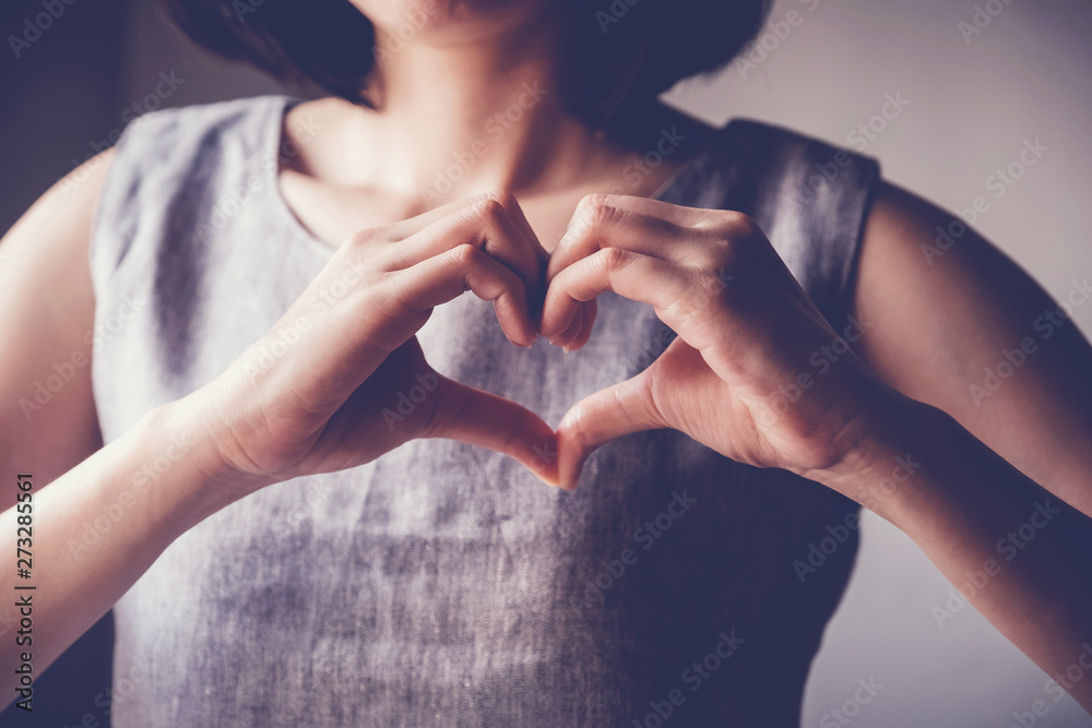 Fototapeta young woman making her hands in heart shape, heart health insurance, social responsibility, donation charity, world heart day, appreciation, world mental health day concept