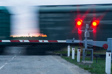 Two Traffic Lights With Red Light And Barrier In The Background Moving Wagons And Sunset