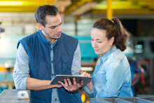 Man And Woman Checking A Tablet In Factory