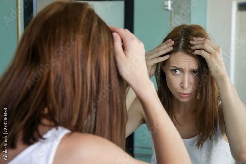 Portrait of a beautiful young woman examining her scalp and hair in front of the Canvas Print