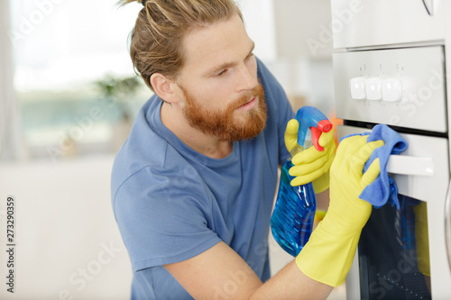 Photo sur Aluminium Individuel man spraying product to clean oven