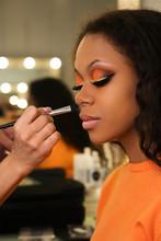 Makeup Artist Applies Foundation For Makeup Of African Girl. Evening Make-up. Closeup Portrait.