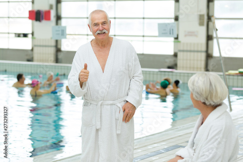 senior couple at indoor pool wearing bathrobes Canvas Print