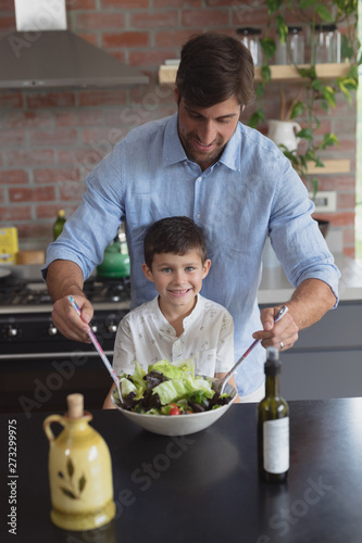 Father and son preparing vegetable salad in kitchen