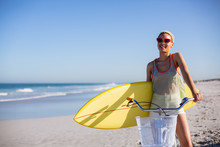 Woman With Surfboard Sitting On Bicycle At Beach In The Sunshine