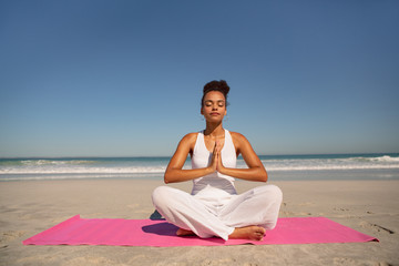 Beautiful woman doing yoga on exercise mat at beach in the sunshine