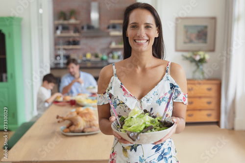 Woman holding a bowl of vegetable salad at home