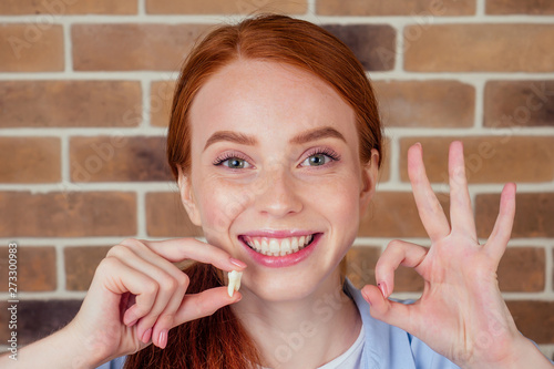 Fotografia redhaired ginger female with snow-white smile holding white wisdom tooth after s